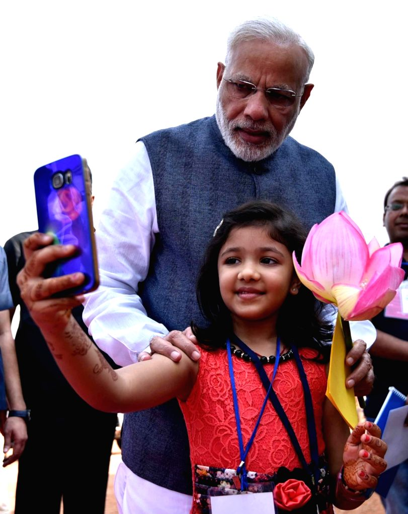 Prime Minister Narendra Modi shares a selfie moment with Devanshi in Raipur who had won a chess tournament and had expressed her desire to meet Prime Minister in Naya Raipur on Nov 1, 2016. - Narendra Modi