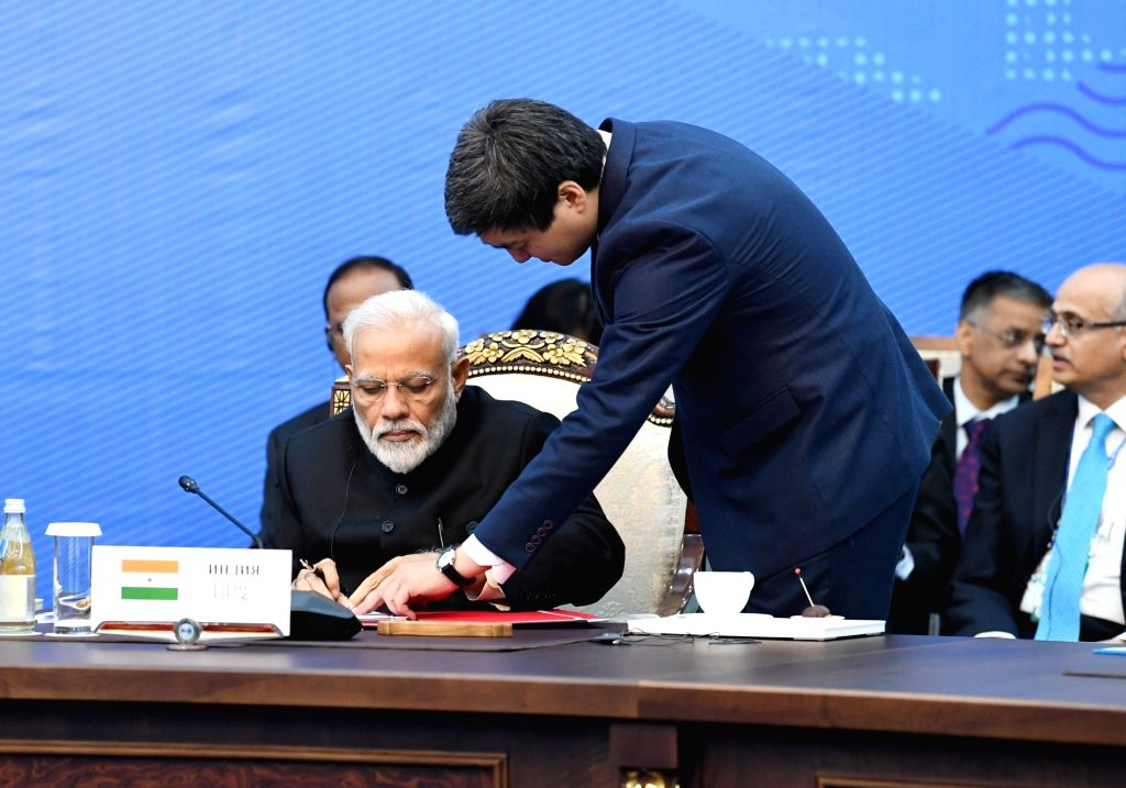Prime Minister Narendra Modi signs documents at the 2019 Shanghai Cooperation Organization (SCO) Summit in Bishkek, Kyrgyzstan on June 14, 2019. - Narendra Modi