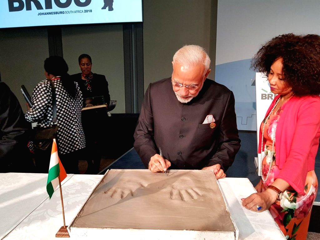 Prime Minister Narendra Modi signs his hand impression on clay, for a symbolic demonstration of our connect to the Cradle of Humankind in Maropeng in South Africa on July 26, 2018. - Narendra Modi