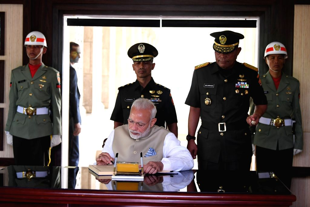Prime Minister Narendra Modi signs the visitor book at the Kalibata National Heroes' Cemetery, in Jakarta of Indonesia on May 30, 2018. - Narendra Modi