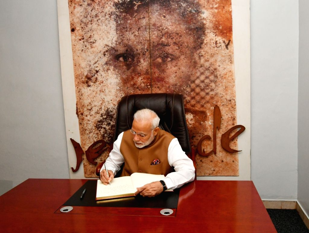 Prime Minister Narendra Modi signs the visitor's book of Kigali Genocide Memorial Centre during his visit to the memorial in Rwanda's Kigali on July 24, 2018. - Narendra Modi