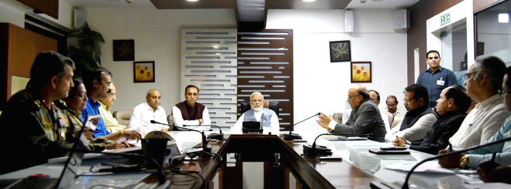 Prime Minister Narendra Modi takes a meeting on the situation arising out of incessant rain and floods in different parts of Gujarat in Ahmedabad on July 25, 2017. Also seen Gujarat Chief ... - Narendra Modi and Nitinbhai Patel