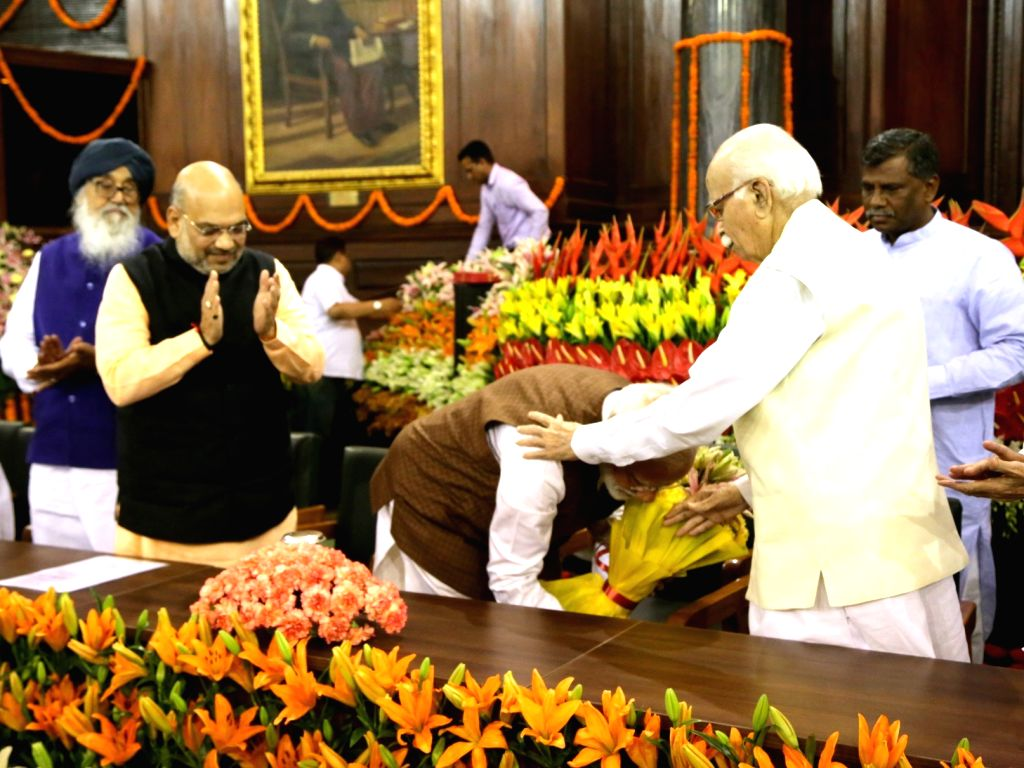 Prime Minister Narendra Modi takes blessings of BJP veteran LK Advani by touching his feet during NDA Parliamentary Board meeting at the Central Hall of Parliament, in New Delhi on May 25, ... - Narendra Modi