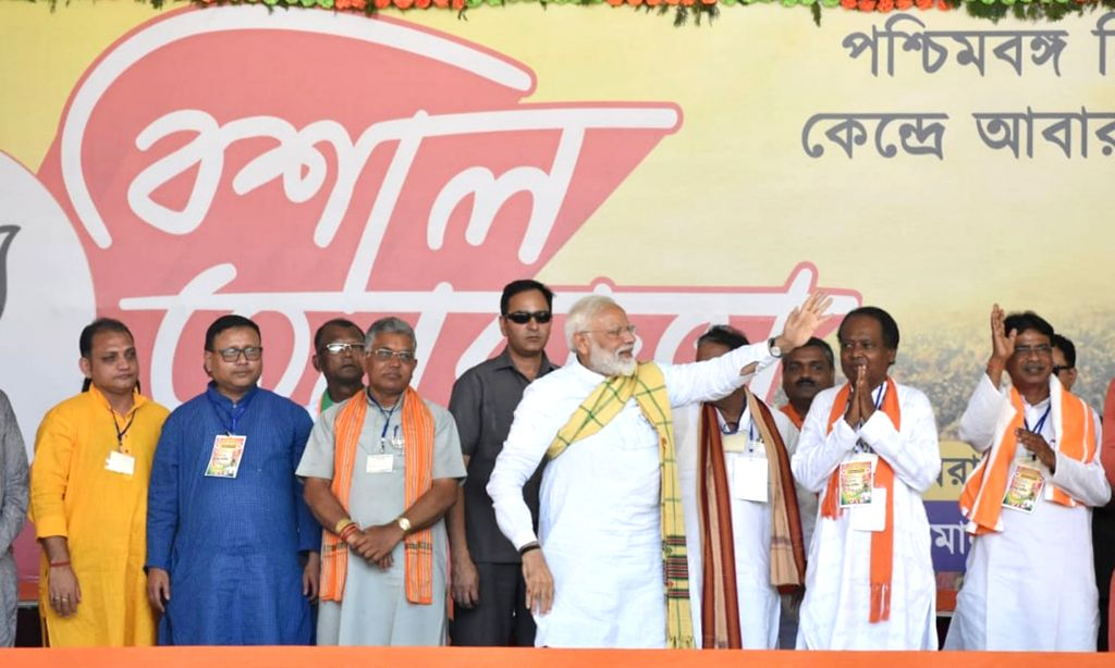 Prime Minister Narendra Modi waves at supporters during a public rally in Jhargram, West Bengal on May 6, 2019. Also seen West Bengal BJP President Dilip Ghosh. - Narendra Modi and Dilip Ghosh