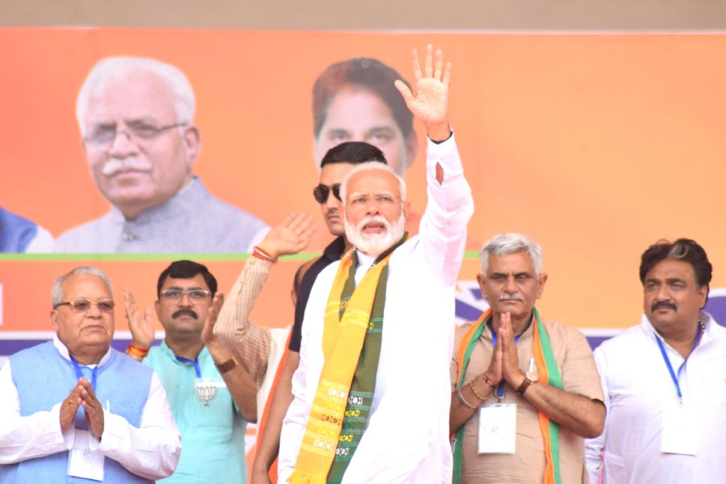Prime Minister Narendra Modi waves at supporters during a public rally in Rohtak, Haryana on May 10, 2019. - Narendra Modi