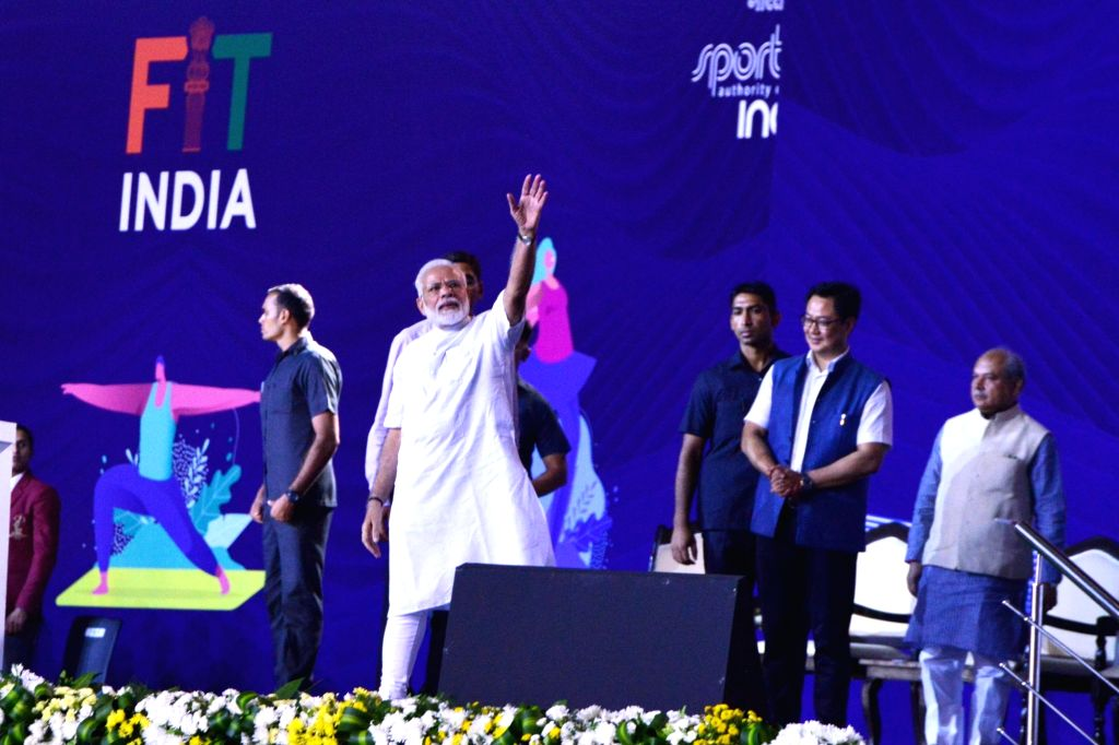 Prime Minister Narendra Modi waves at the audience at the launch of a nation-wide 'Fit India Movement' in New Delhi on Aug 29, 2019. Also seen Union MoS Youth Affairs and Sports Kiren ... - Narendra Modi