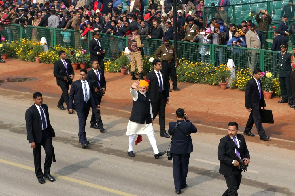 Prime Minister Narendra Modi waves to the cheering crowd as he walks along the Rajpath to greet the people after the Republic Day parade, in New Delhi on Jan 26, 2018. Modi, was attired in ... - Narendra Modi