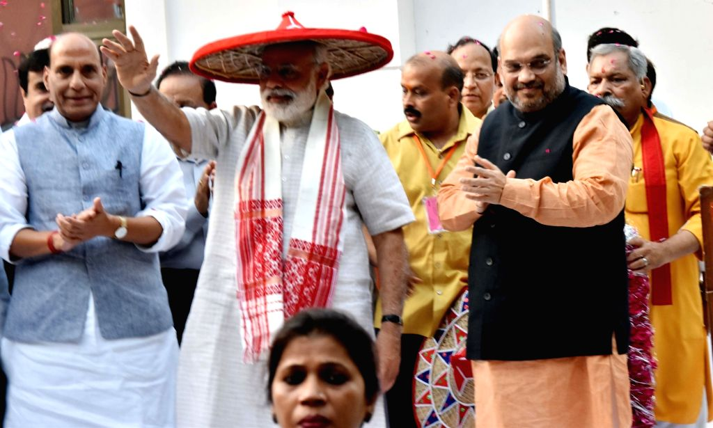 Prime Minister Narendra Modi wearing Japi -a traditional headgear of Assam- flanked by Union Home Minister Rajnath Singh and BJP chief Amit Shah at BJP head office in New Delhi on May 19, ... - Narendra Modi, Rajnath Singh and Amit Shah