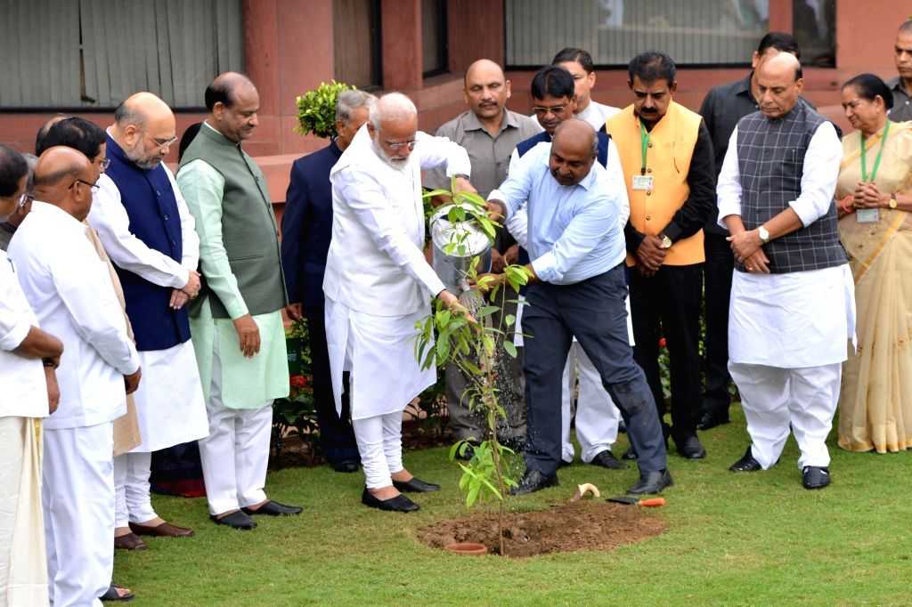 Prime Minister Narendra Modi with his cabinet colleagues, Lok Sabha Speaker Om Birla and Members of Parliament plant a sapling during a tree plantation drive at Parliament House in New ... - Narendra Modi