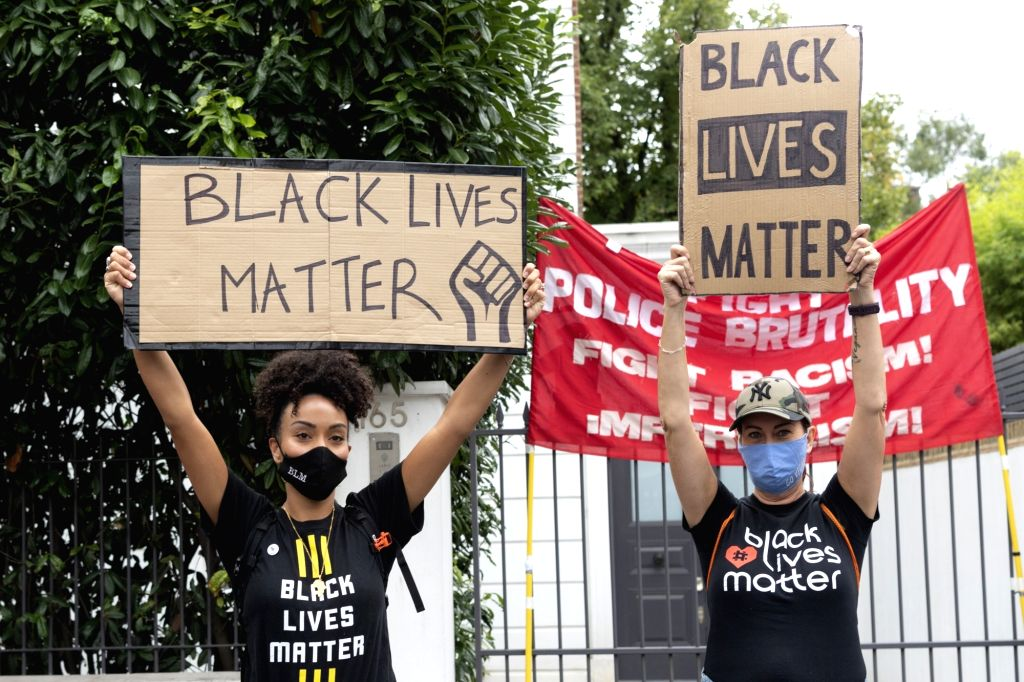 Protesters hold placards with anti-racism messages during the Million People March demonstration in London, Britain, Aug. 30, 2020. Hundreds of demonstrators took to ...