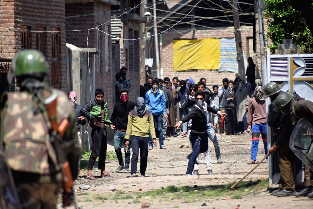 Protesters pelt stones on security personnel during Srinagar Lok Sabha by-poll, in Srinagar on April 9, 2017.