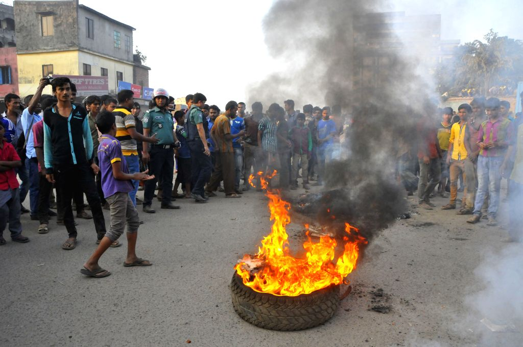 Protesters set a fire on a tyre during a protest in Dhaka, Bangladesh, Nov. 29, 2015. Hundreds of Bangladeshi truckers Sunday staged mass protests against a drive to ...