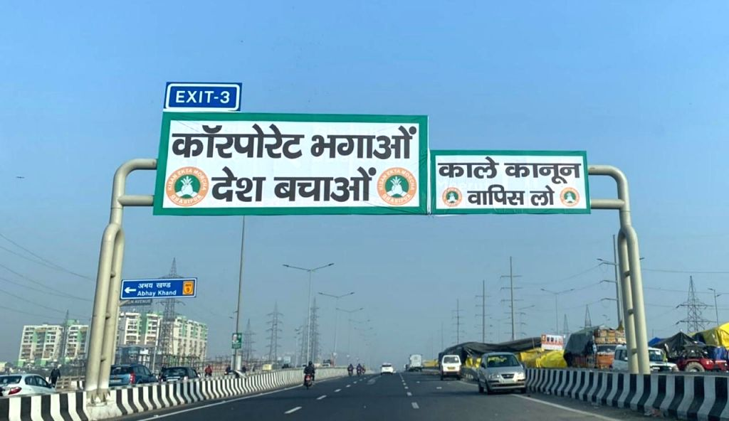 Protesting farmers affix 'black laws' banners on NH signboards