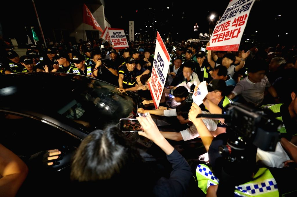 Protesting his release, citizens try to block the car carrying Kim Ki-choon, a former presidential chief of staff, leaving a detention center in eastern Seoul on Aug. 6, 2018, as his custody ...