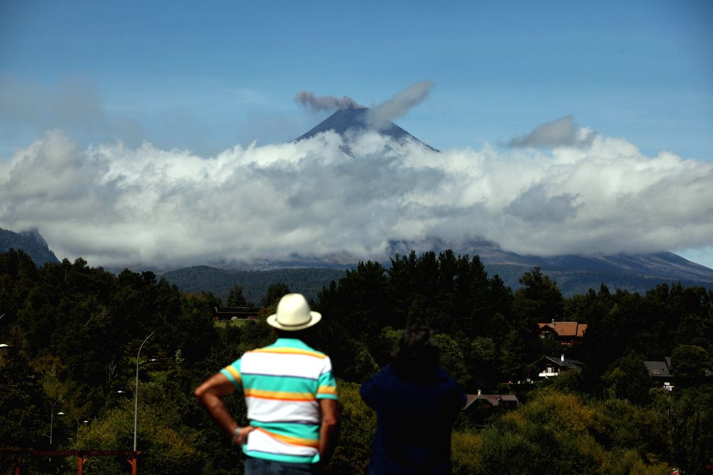 A person watches an ash column rising from the Villarrica volcano, located 18km south of Pucon, in the Araucania Region, Chile, on March 19, 2015. Chile's National ...