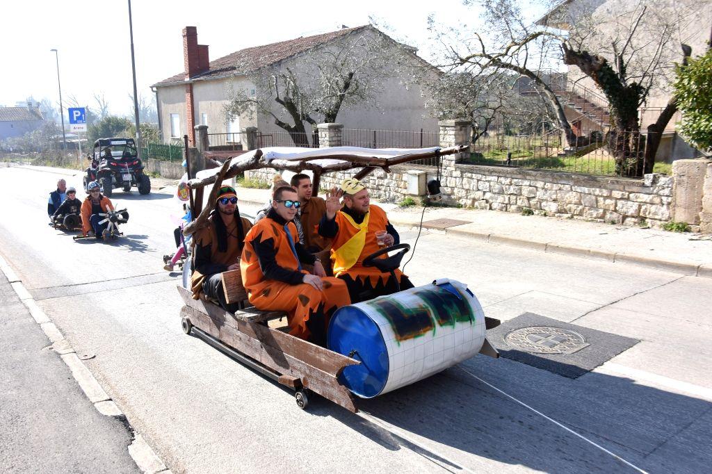 "PULA (CROATIA), Feb. 17, 2019 People take part in the ""Balinjerada"" race during a carnival parade in Pula, Croatia, on Feb. 17, 2019."