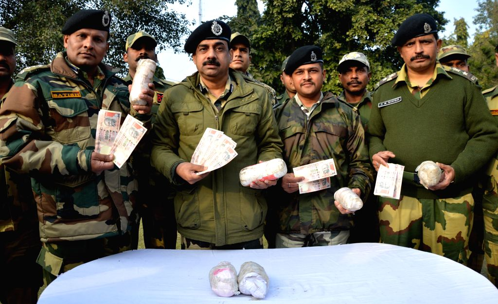BSF officials display 7 kg heroin worth around Rs 35 crores in the international market and counterfeit currency notes with a face value of 38000 recovered from Indo-Pak border in Punjab on ..