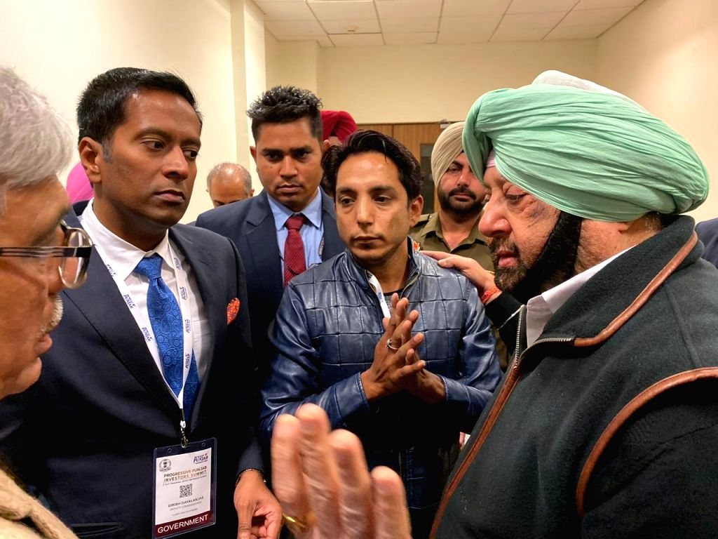 Punjab Chief Minister Amarinder Singh listens to grievances of man who reached close to him after breaching his high security at a function in Mohali. - Amarinder Singh