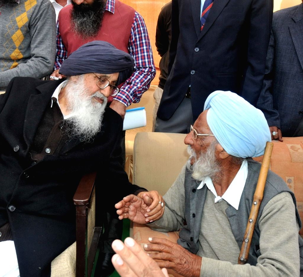 Punjab Chief Minister Parkash Singh Badal interacts with a villager during Sangat Darshan Function in Lambi of Junjab on Dec.6, 2013.