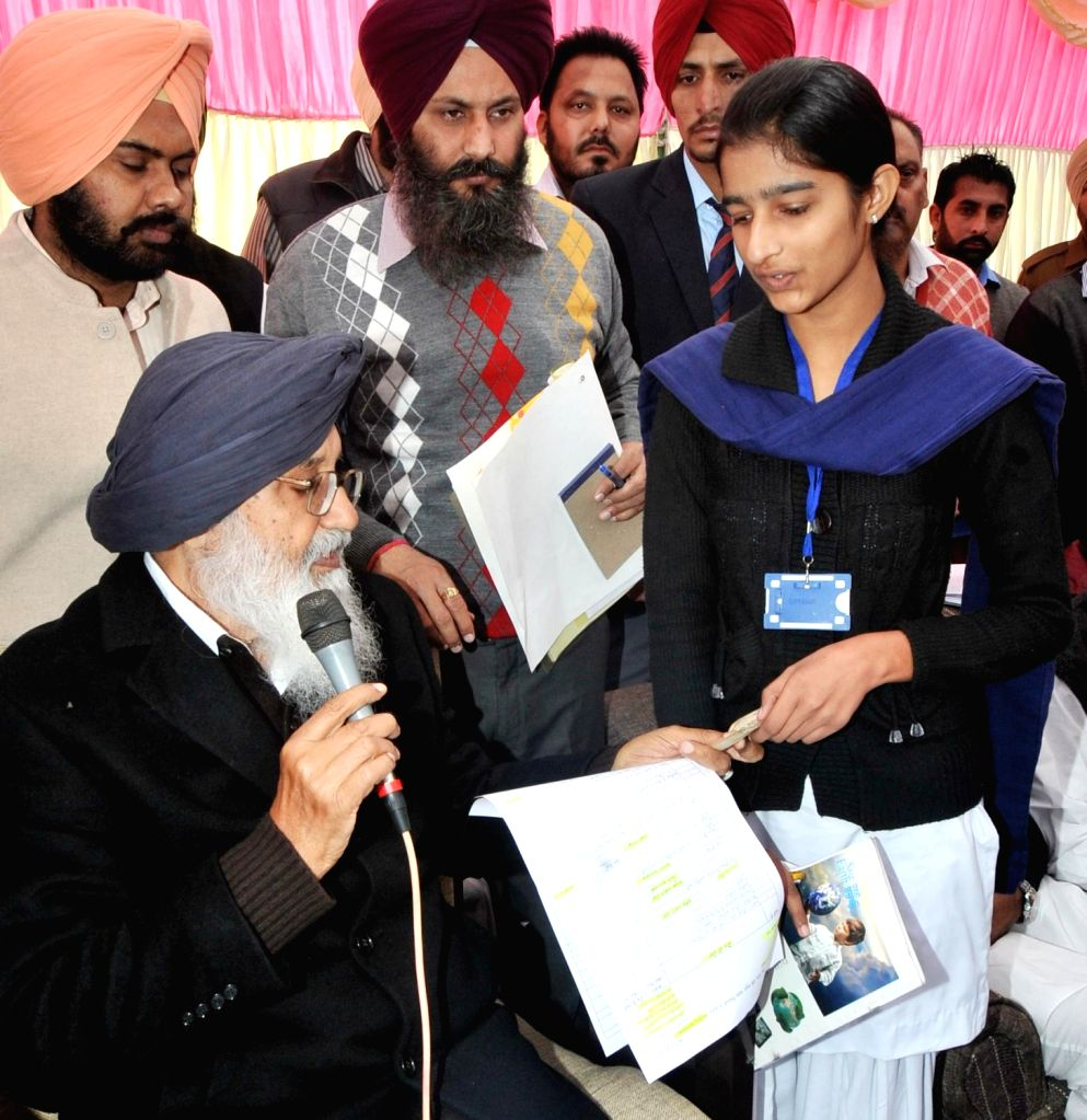 Punjab Chief Minister Parkash Singh Badal honours Kiranjit Kaur a Government Senior Secondary School student during Sangat Darshan Function  in Lambi of Junjab on Dec.6, 2013. - Kiranjit Kaur