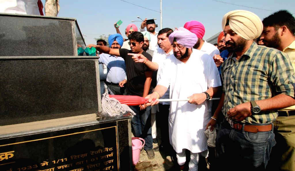 Punjab Congress chief Captain Amarinder Singh cleans the statue of Subedar Nand Singh a recipient of Victoria Cross and Mahavir Chakra at Fauji Chowk in Bathinda on Oct 19, 2016. - Amarinder Singh and Subedar Nand Singh