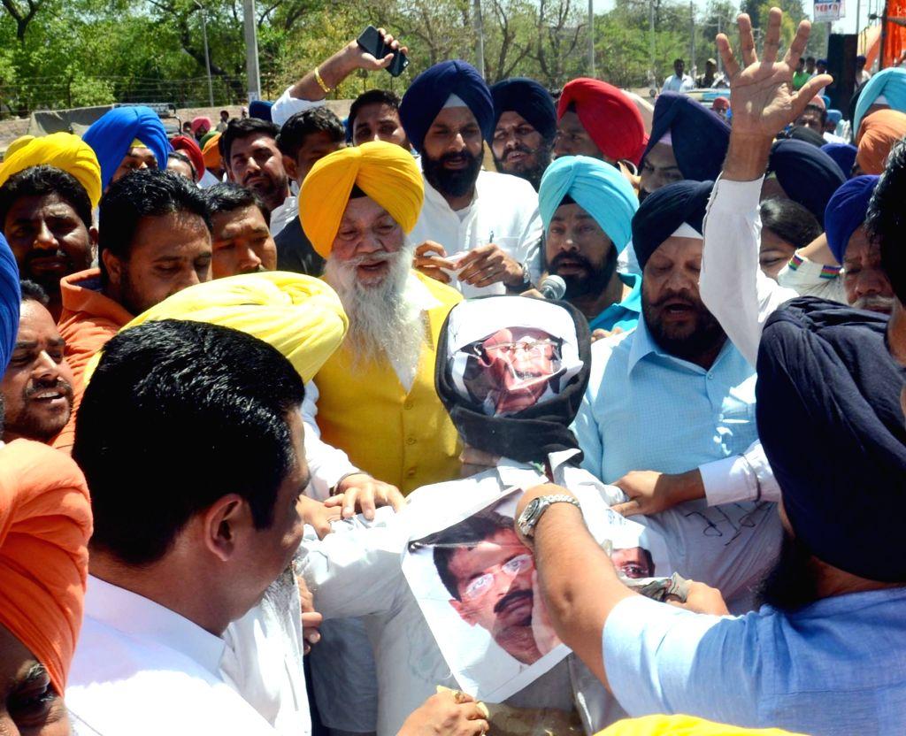 Punjab Minister Bikram Singh Majitihia and other Shiromani Akali Dal leaders burn an effigy of Delhi Chief Minister and AAP leader Arvind Kejriwal in Majitha near Amritsar on April 12, 2016. - Bikram Singh Majitihia and Arvind Kejriwal