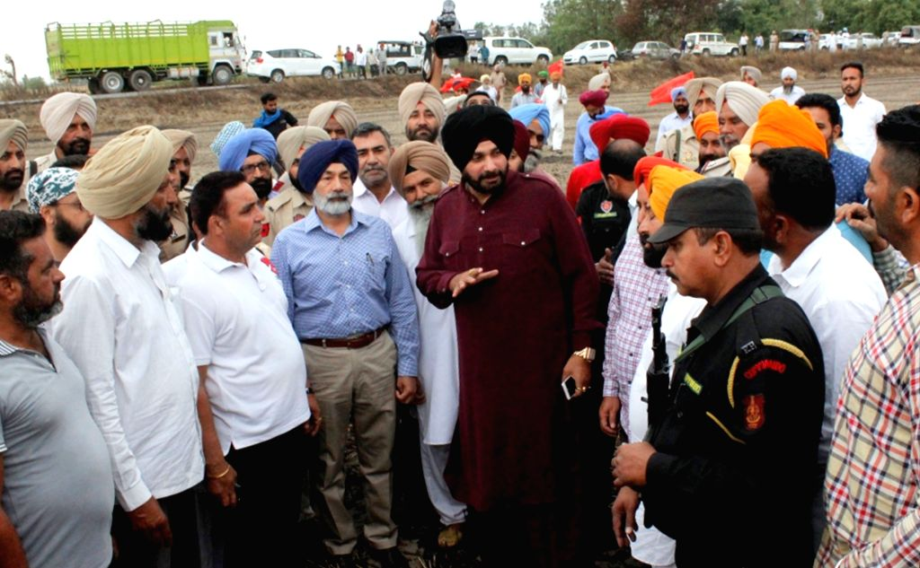 Punjab Minister Navjot Singh Sidhu takes stock of the situation during his visit to a field where standing wheat crop were destroyed in a fire near Amritsar on April 23, 2017. - Navjot Singh Sidhu