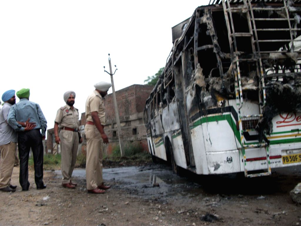 Punjab police personnel inspect a bus which was set on fire by the residents of Guruwali village, 15 km away from Amritsar on April 15, 2014. A villager was killed after being hit by the bus.