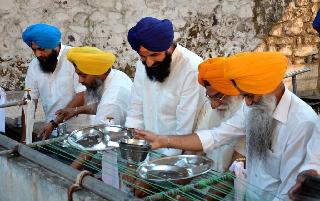 "Punjab Revenue Minister Bikram Singh Majithia perform 'seva' at Takht Sri Kesgarh Sahib as a punishment for distorting the ""Gurbani"" in Anandpur Sahib on May 6, 2014."