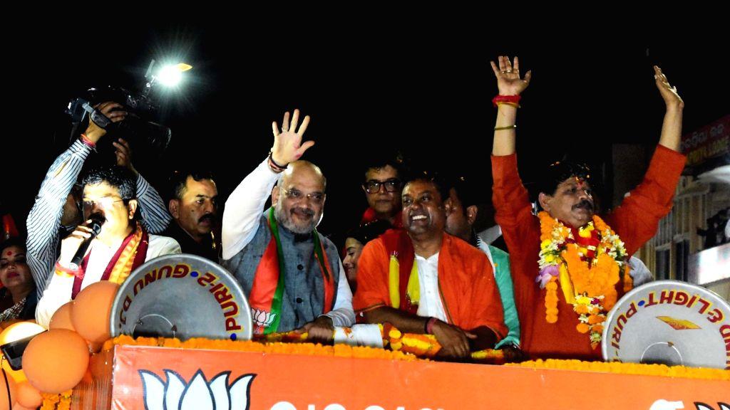 Puri: BJP chief Amit Shah during a roadshow ahead of 2019 Lok Sabha elections in Puri, Odisha on April 9, 2019. Also seen BJP leaders Dharmendra Pradhan and Sambit Patra. (Photo: IANS) - Amit Shah