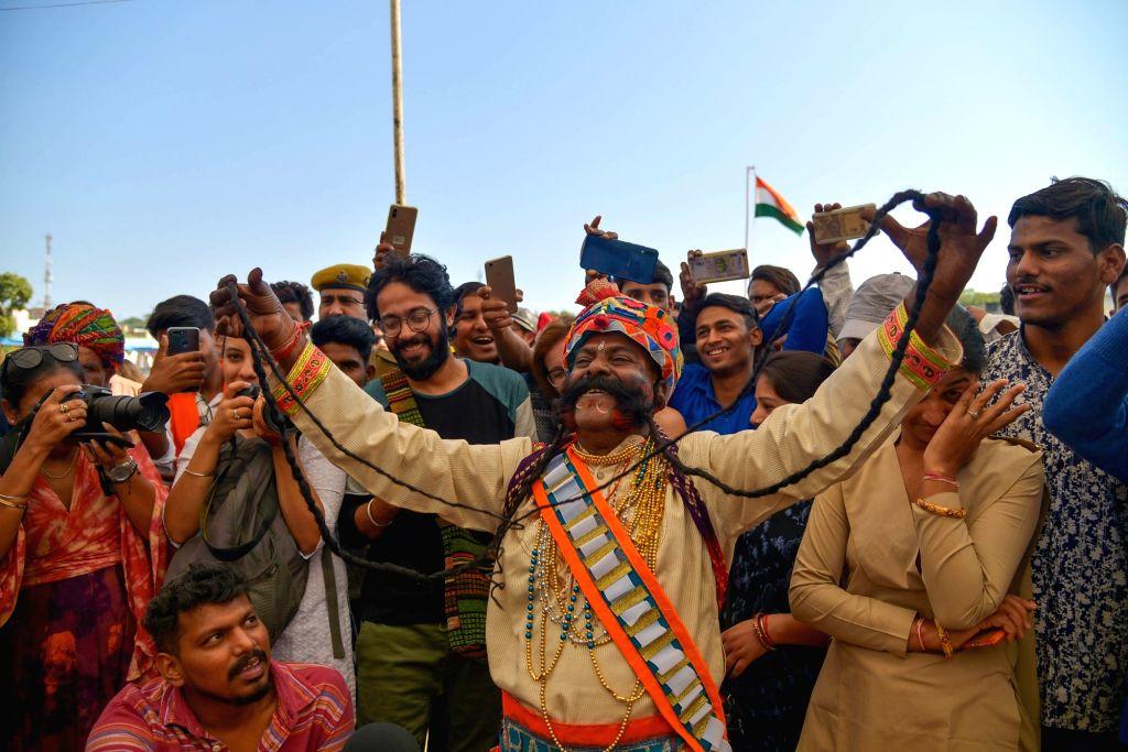 Pushkar: A man showcases his long mustache during a competition at Pushkar Camel Fair 2018, on Nov 20, 2018. (Photo: Shaukat Ahmed/IANS)