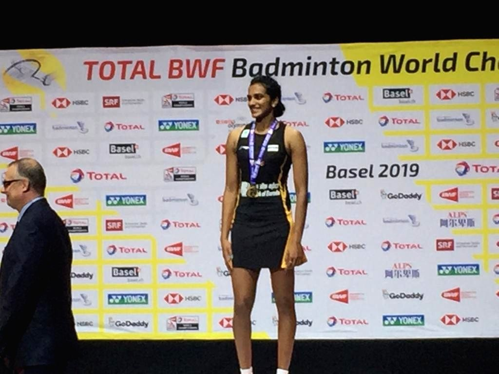 PV Sindhu celebrates on the podium during the awarding ceremony of the women's singles final of BWF World Championships at St. Jakobshalle in Basel, Switzerland on Aug 25, 2019.