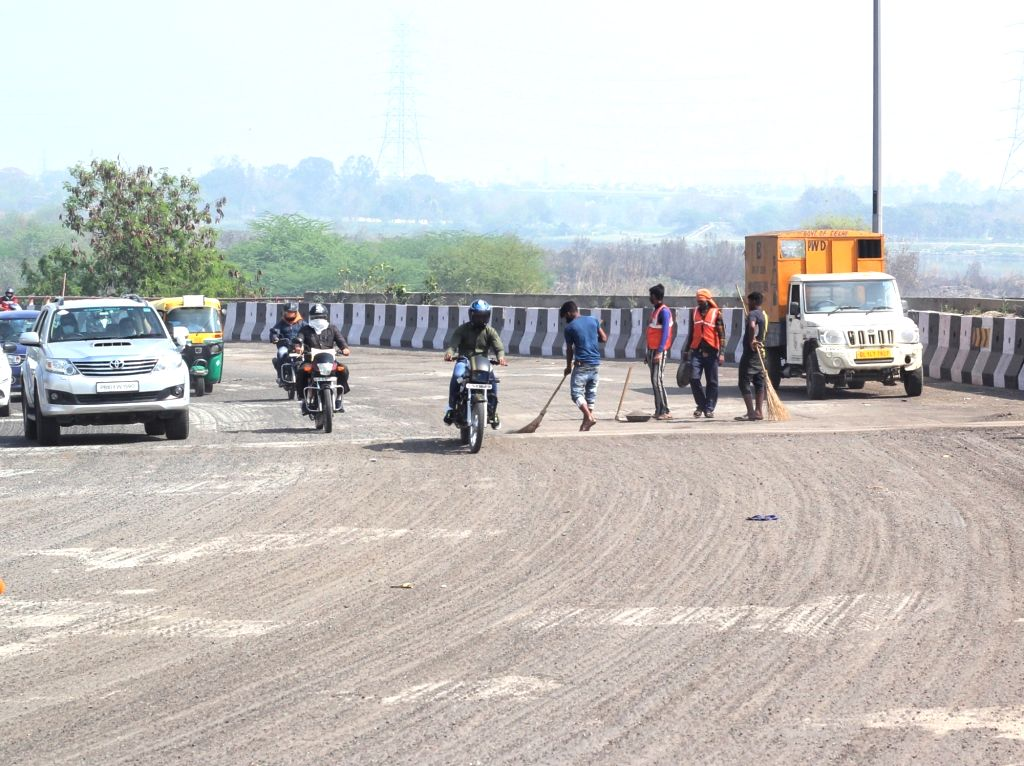 PWD workers cleaning the road before road renovation near Power house Salimgarh fort road in new Delhi.
