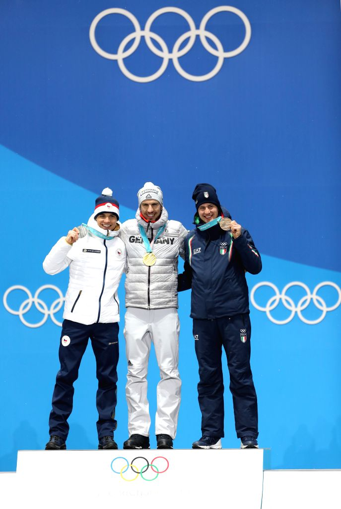 PYEONGCHANG, Feb. 13, 2018 - Champion Arnd Peiffer from Germany (C), second-placed Michal Krcmar from Czech Republic (L) and third-placed Dominik Windisch from Italy pose for photos during the medal ...