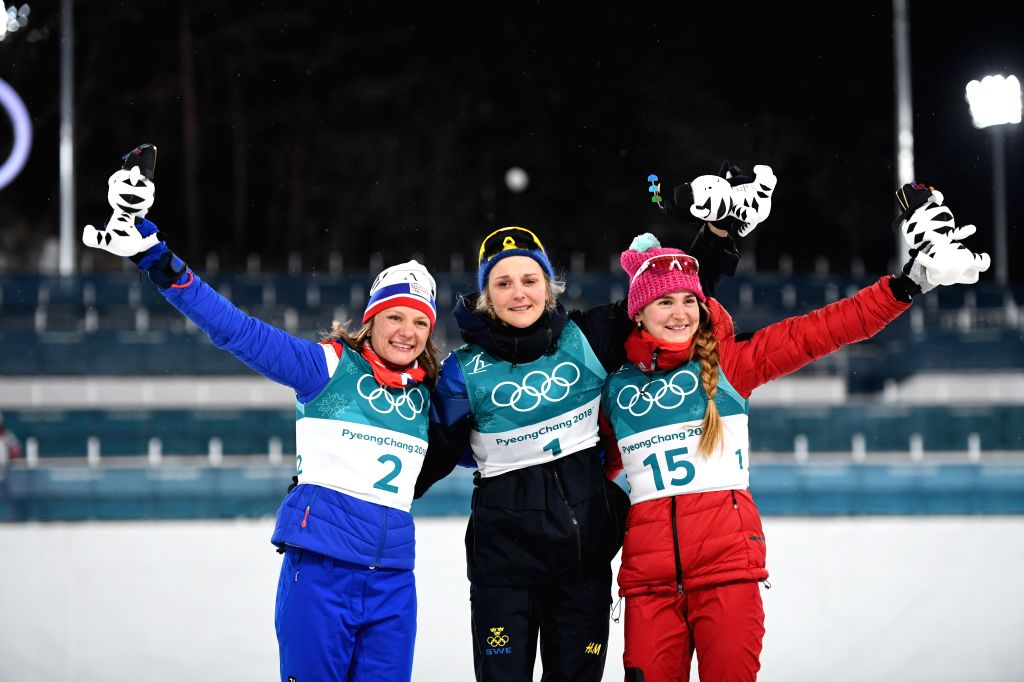 PYEONGCHANG, Feb. 13, 2018 - Champion Stina Nilsson (C) from Sweden, second-placed Maiken Caspersen Falla (L) from Norway and third-placed Olympic athlete from Russia Yulia Belorukova pose for photos ...