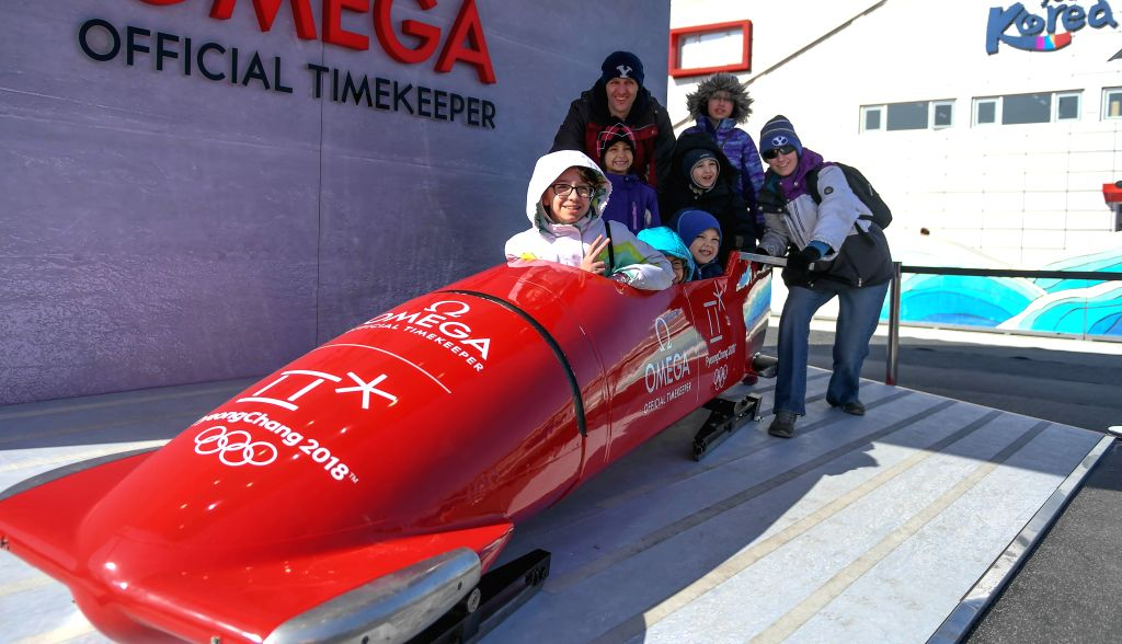 PYEONGCHANG, Feb. 13, 2018 - Visitors pose for photos with a bobsleigh at the Gangneung Olymic Park, South Korea, on Feb. 13, 2018. As the 2018 PyeongChang Winter Olympic Games is being held from ...