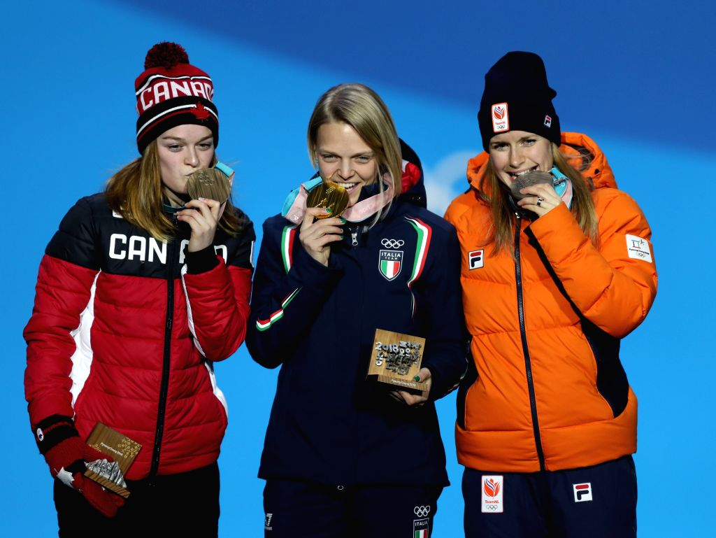 PYEONGCHANG, Feb. 14, 2018 - Champion Italy's Arianna Fontana (C), second-placed Yara Van Kerkhof from the Netherlands (R) and third-placed Canada's Kim Boutin pose for photos during medal ceremony ...