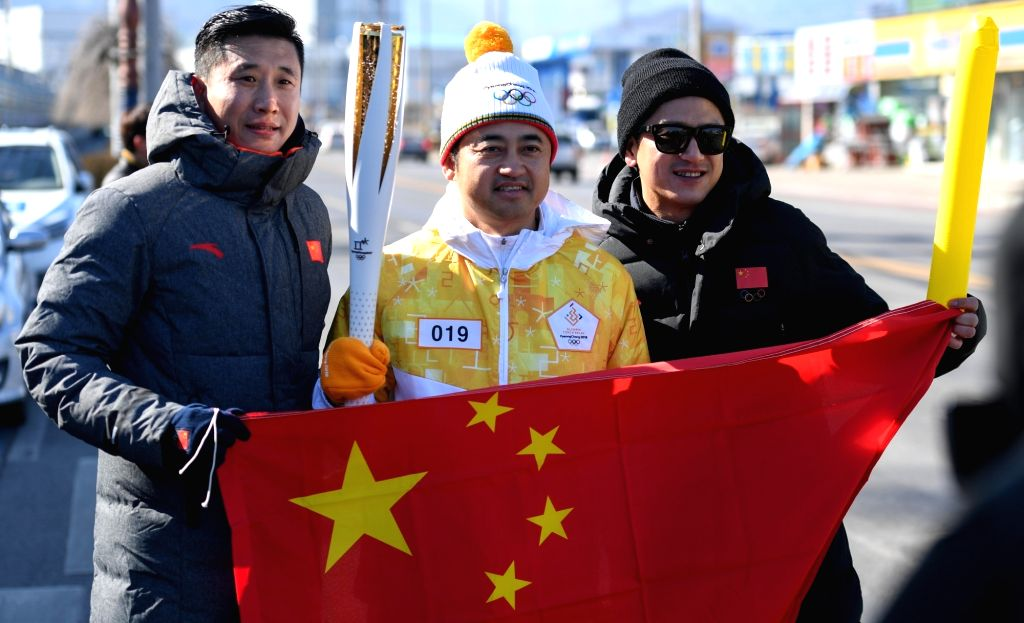 PYEONGCHANG, Feb. 6, 2018 - Chinese torch bearer Ding Shizhong (C) presents Chinese national flag during the Olympic Torch Relay in Donghae, Gangwon-do province, South Korea, Feb. 6, 2018. The 2018 ...