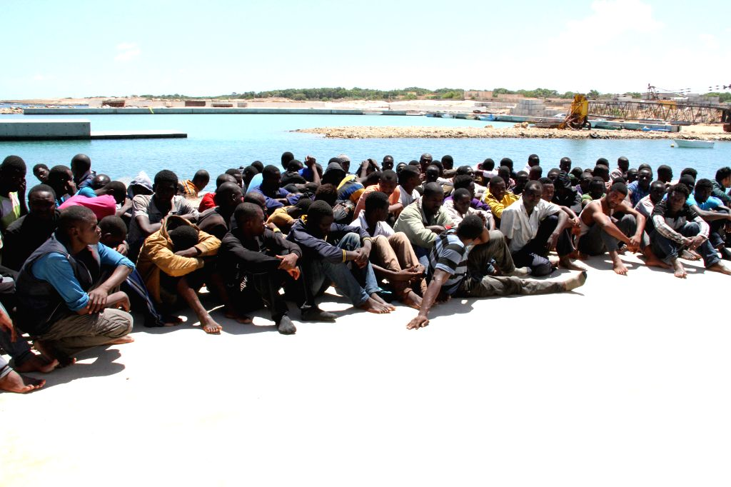 Some illegal immigrants sit on the ground after being rescued off the coast of Qara Bolle, in Libya, on July 17. Libya's coast guard rescued some 100 illegal ...