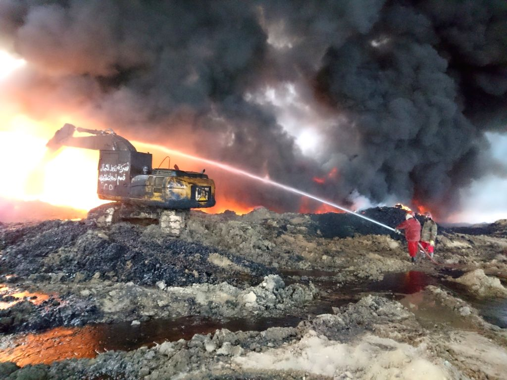 QAYYARAH, Nov. 26, 2016 - Oil company workers try to put off fire at an oil well in Qayyarah town, south of Mosul, in northern Iraq, on Nov. 26, 2016. Qayyarah town is seized by the Islamic State ...