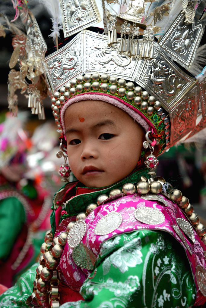 QIANDONGNAN, Oct. 13, 2016 - A kid of Dong ethnic group in traditional costumes partiticaptes in a folk performance to celebrate the opening of the China Traditional Village Qiandongnan Summit held ...