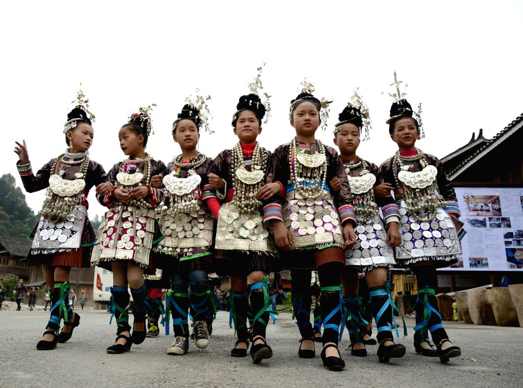 QIANDONGNAN, Oct. 13, 2016 - Girls of Dong ethnic group in traditional costumes partiticapte in a folk performance to celebrate the opening of the China Traditional Village Qiandongnan Summit held in ...