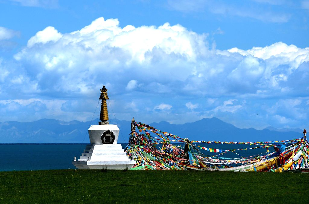 Photo taken on July 23, 2014 shows a white tower and prayer flags by the Qinghai Lake, northwest China's Qinghai Province.