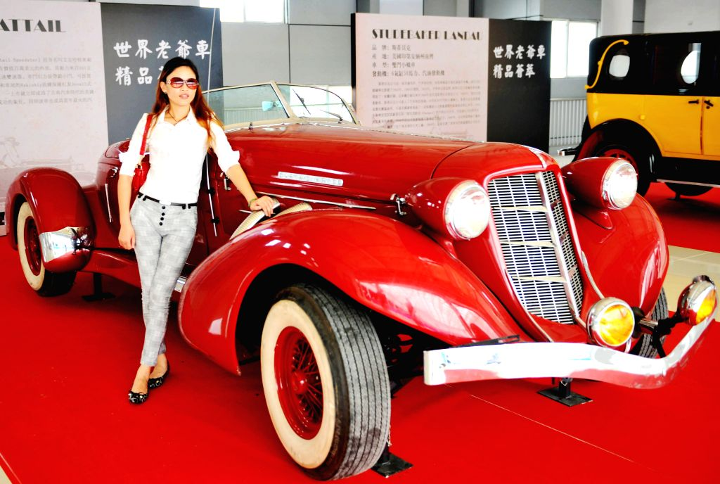 A visitor poses for photos with an Auburn classic car during a vintage car show in Qinzhou International Automobile City in Qinzhou, south China's Guangxi Zhuang ..