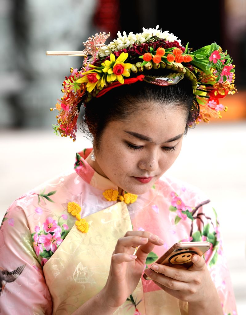"""QUANZHOU, April 10, 2017 - A """"Xunpu"""" woman browses her cellphone in Xunpu Village of Quanzhou City, southeast China's Fujian Province, April 9, 2017. """"Xunpu"""" women, who are ..."""