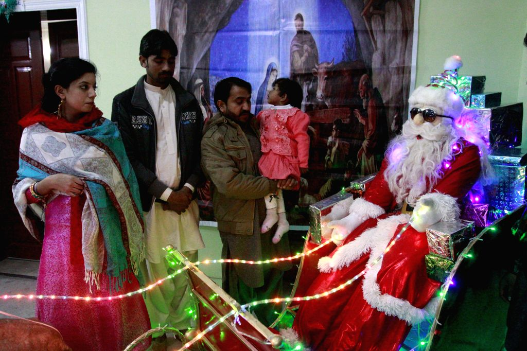Pakistani Christians look at a decoration after a Christmas mass at a church in southwest Pakistan's Quetta, Dec. 25, 2014. Christians around the world are ...