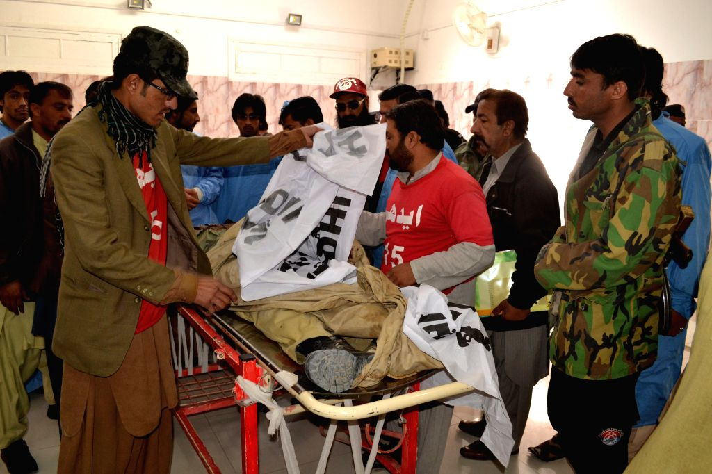 Rescuers examine the body of a policeman at a hospital following an attack on a polio vaccination center in southwest Pakistan's Quetta, Feb. 4, 2015. At least one ...
