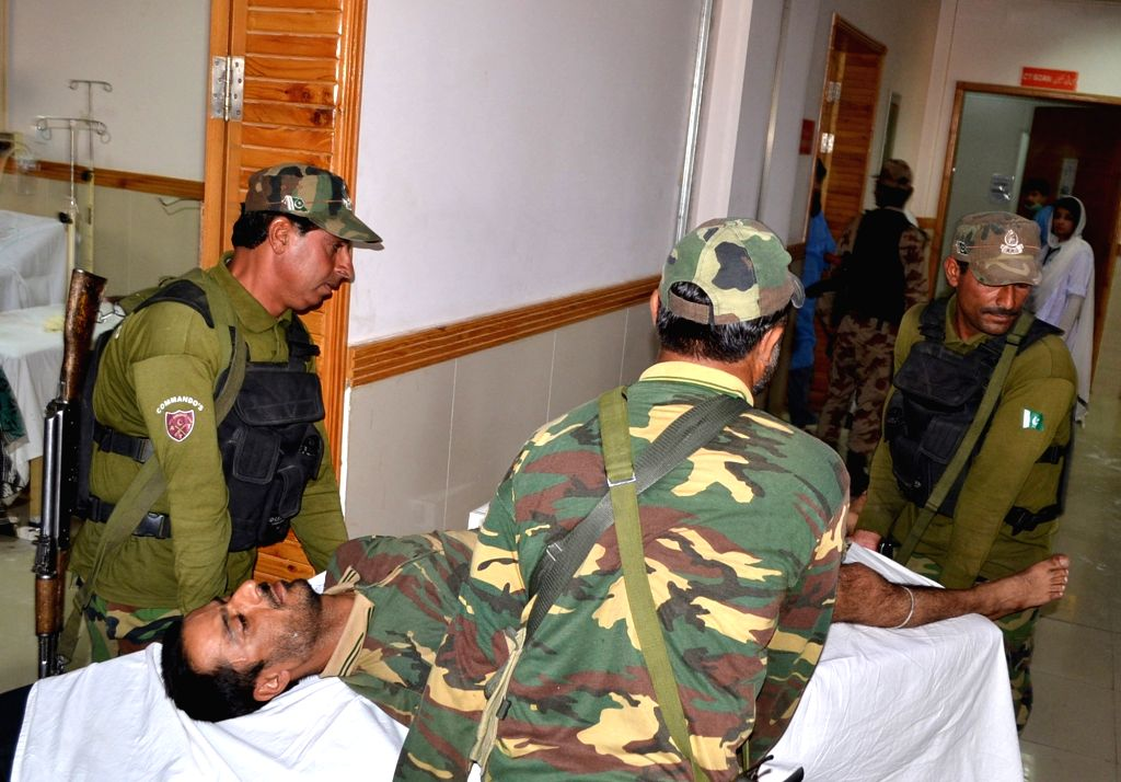 QUETTA, June 23, 2017 - Security officers transfer their injured colleague to a hospital following a suicide blast in southwest Pakistan's Quetta, on June 23, 2017. At least 11 people including five ...