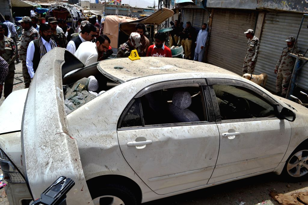 QUETTA, June 24, 2016 - Security officials examine a damaged vehicle at a blast site in southwest Pakistan's Quetta, June 24, 2016. At least three people were killed and 27 others injured as a bomb ...