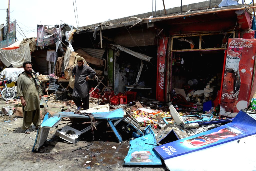 QUETTA, June 24, 2016 - Shopkeepers examine their damaged shops at a blast site in southwest Pakistan's Quetta, June 24, 2016. At least three people were killed and 27 others injured as a bomb blast ...